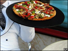 Waiter serving pizza
